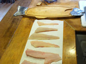 Freshly caught Blackfish and Fluke fillets being prepared for the grill.