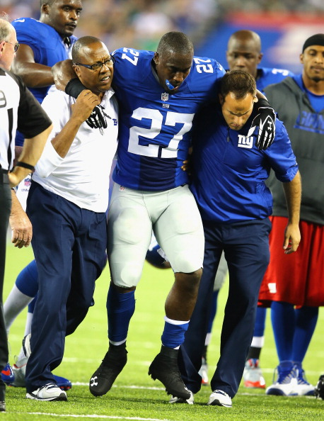 EAST RUTHERFORD, NJ - AUGUST 24:  Stevie Brown #27 of the New York Giants is helped off the field after injuring his leg after making an interception against  Geno Smith #7 of the New York Jets  during their pre season game at MetLife Stadium on August 24, 2013 in East Rutherford, New Jersey.